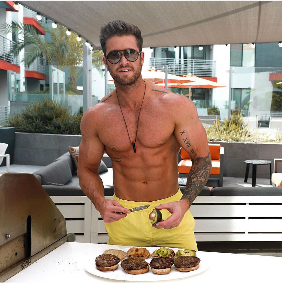 A male bodybuilder preparing hamburgers on the grill for a good protein meal.